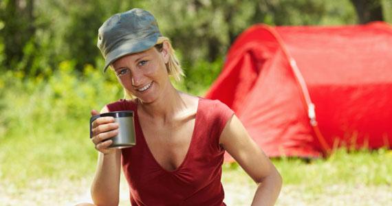 Das ist eine 26jährige Frau. Sie trägt eine graue Mütze und ein rotes, ärmelloses Shirt. In der rechten Hand hält sie einen Becher, der zu einer Thermoskanne gehört. Sie lächelt in die Kamera. Rechts im Hintergrund ist ein rotes Zelt zu sehen. Der restliche Hintergrund ist grün und unscharf. Die Frau litt unter starkem PMS-Syndrom und hat sich bei Brigitte Weber, TCM-Gynäkologie in 8032 Zürich erfolgreich mit Akupunktur behandeln lassen.