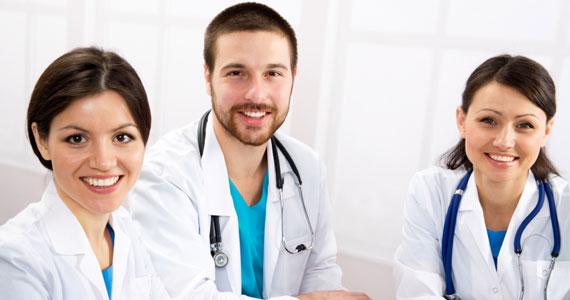 Das Bild zeigt einen jungen Mann und zwei junge Frauen. Alle tragen einen weissen Arztkittel. Eine der beiden Frauen litt unter extremer Dysmenorrhoe.