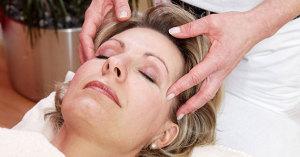 Akupressur Behandlung am Kopf einer Patientin