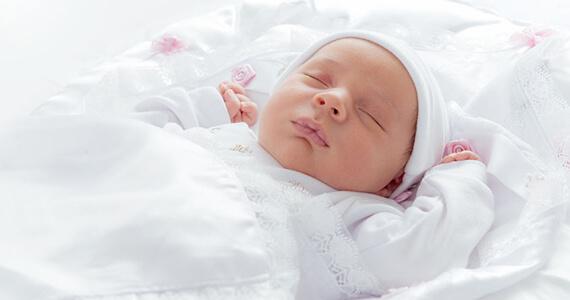 Ein neugeborenes Kind liegt ganz in weiss in seinem Bettchen.