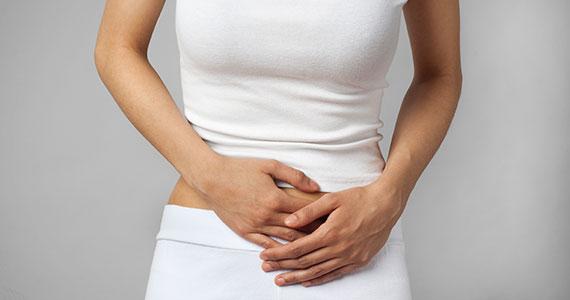 Eine Frau mit Messbeschwerden hält sich den schmerzenden Bauch.