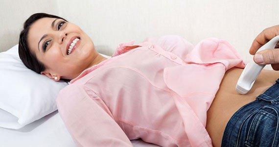Eine junge Frau mit kurzen schwarzen Haaren und einer rosa Bluse wird von ihrer Gynäkologin mit Ultraschall untersucht.