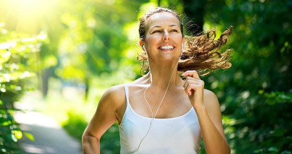 Eine junge Frau mit Kopfhörern im Ohr joggt an einem sonnigen Tag in einem weissen, ärmellosen T-Shirt an grünen Bäumen vorbei.