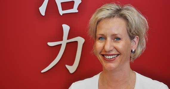 TCM-Gynäkologin Brigitte Weber steht vor einer roten Wand in ihrer Praxis. Im Hintergrund sind die beiden chinesischen Zeichen für «Lebenskraft» zu sehen.