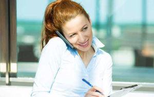 Eine junge Frau mit Pferdeschwanz klemmt ein Smartphone zwischen Schulter und Ohr und notiert sich gleichzeitig etwas auf einem Block.