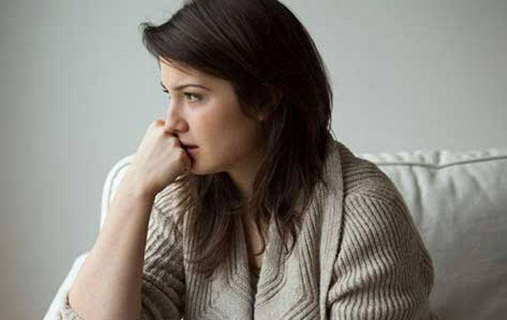Nachdenkliche Frau sitzt auf einem Sofa