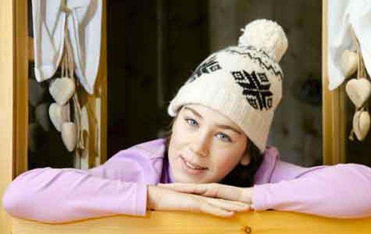 Das Bild zeigt eine 14jährige Frau mit Wollmütze und rosarotem Pullover, die aus einem Fenster mit Holzrahmen blickt.