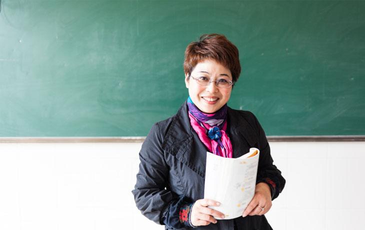 Das ist eine 44jährige Frau mit kurzen, braunen Haaren. Sie trägt eine Brille sowie ein rosafarbenes Foulard und steht vor einer grünen Wandtafel
