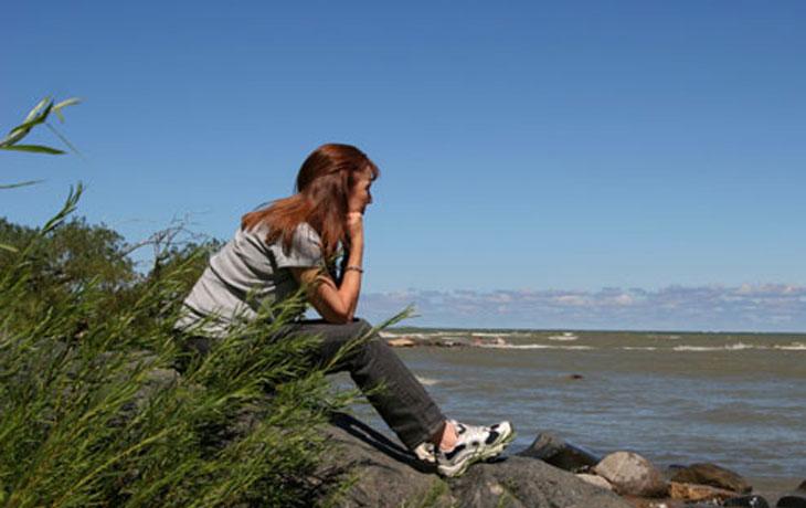 Das ist eine Frau in den Wechseljahren. Sie hat lange, rot-braune Haare und sitzt auf einem Stein am Ufer eines Meeres.
