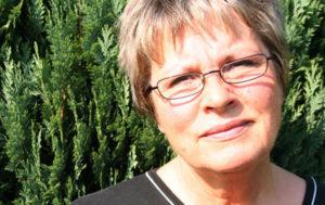Das ist eine 47jährige Frau mit kurzen, hellbraunen Haaren. Sie trägt eine feine, schwarze Brille und steht nachdenklich vor einem grünen Strauch.