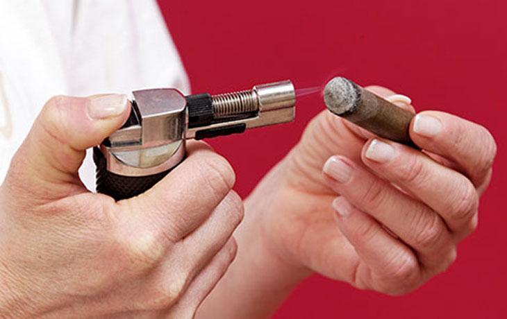 Brigitte Weber hält in der rechten Hand ein Feuerzeug und in der linken Hand eine Moxa Zigarre. Die Flamme zündet die Zigarre an.