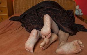 Das sind die Füsse von einem Mann und einer Frau, die unter einer leichten, dunkelbraunen Decke in einem Bett liegen