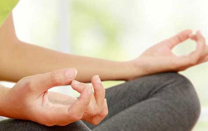 Eine Frau hält ihre Hände auf die Knie, formt mit den Fingern ein Oval und meditiert.
