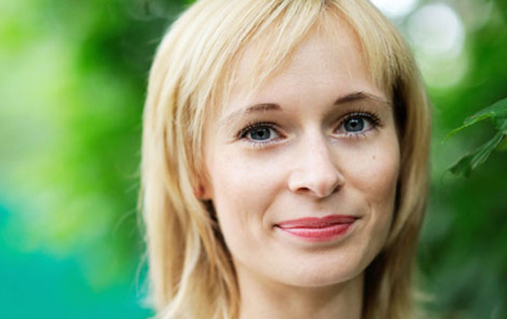 Das ist eine 30jährige Frau mit schulterlangen, dunkelblonden Haaren, dunklen Augen und hellrot geschminkten Lippen.