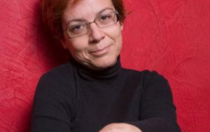 Das ist eine 41jährige Frau. Sie trägt eine eckige Brille und einen schwarzen Pullover. Sie lächelt leicht und steht vor einer roten Wand.