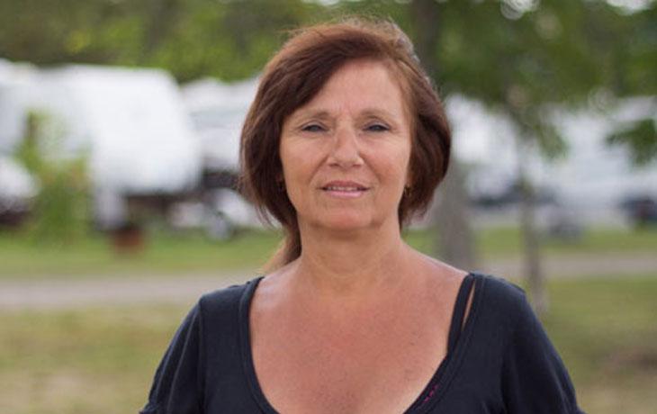 Das ist eine 54jährige Frau mit schulterlangen, rot-braunen Haaren. Sie hat die Augen leicht zusammengekniffen und blickt irritiert in die Kamera.