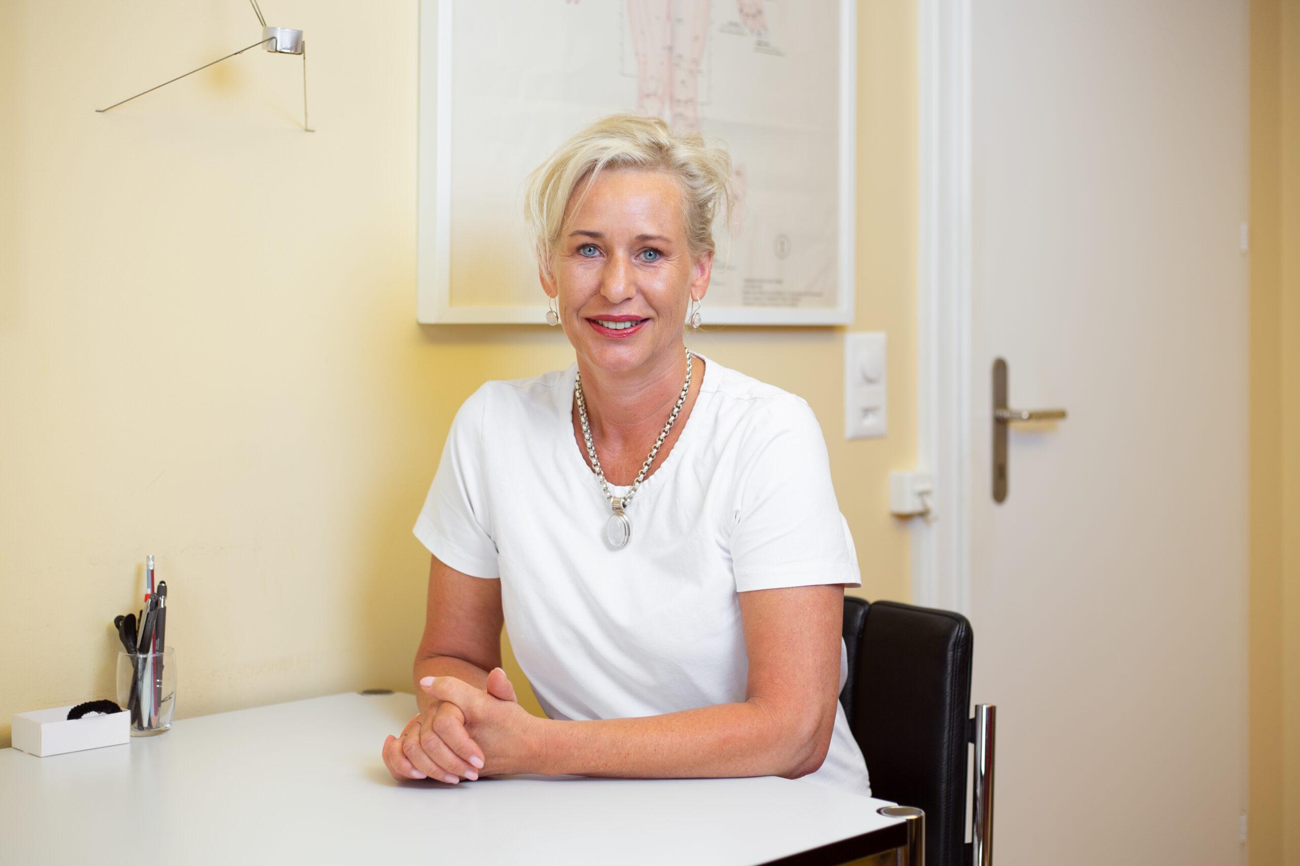 TCM-Gynäkologin Brigitte Weber sitzt an einem Tisch vor einer gelben Wand in ihrer Praxis.